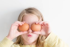 girl holding two eggs while putting it on her eyes