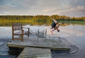 man in black tank top and black shorts jumping on water during daytime